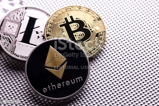 izmir, Turkey - January 15, 2018 Close up shot of three main cryptocurrencies; bitcoin, ethereum and litecoin in metallic surface.