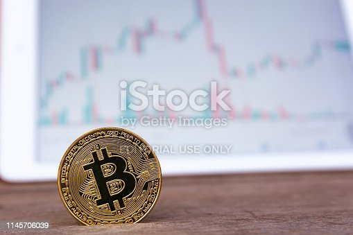 istock Bitcoin gold coin and candlestick chart background 1145706039