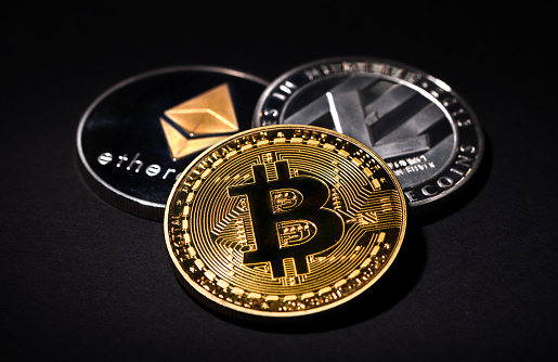 İstanbul, Turkey - February 19, 2018: Close up shot of Bitcoin, Litecoin and Ethereum memorial coins on a black background. Bitcoin, Litecoin and Ethereum are crypto currencies and worldwide payment systems.