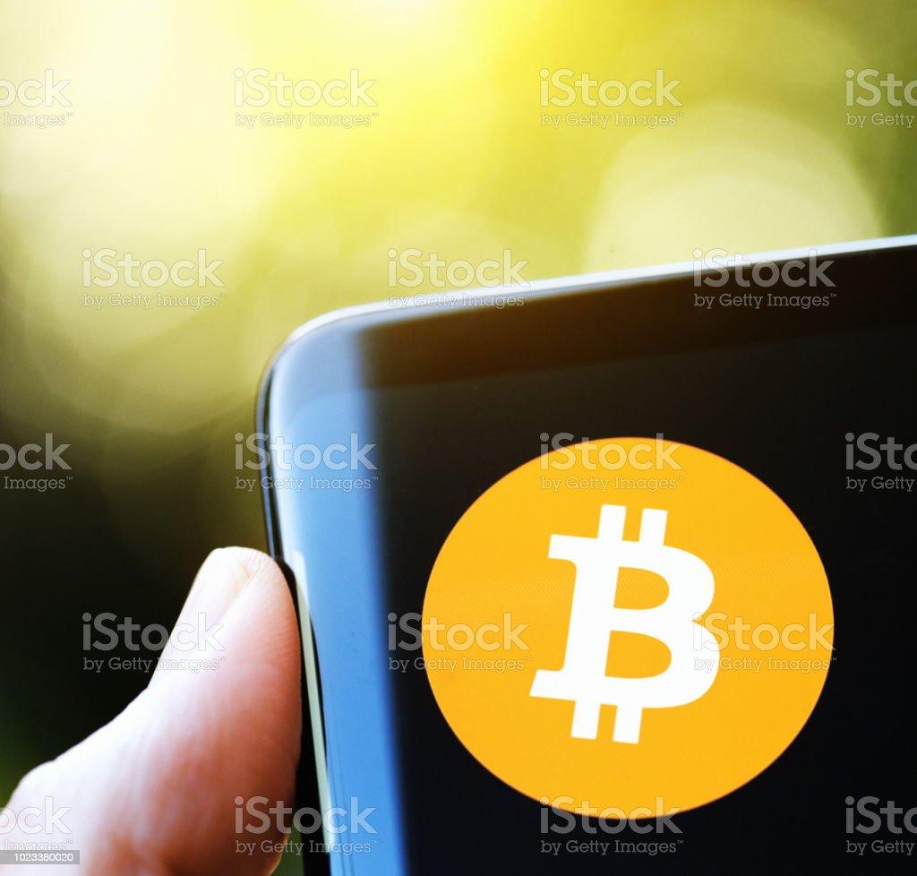 Bitcoin  logo on otherwise blank black phone screen stock photo