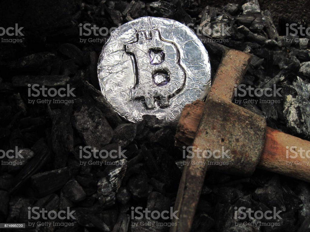 Bitcoin mining. A mine with real hardware. Symbols of block chain technology for crypto currency – metal coin, coal, pickaxe Background for cryptocurrency and ICO transactions Ash Stock Photo