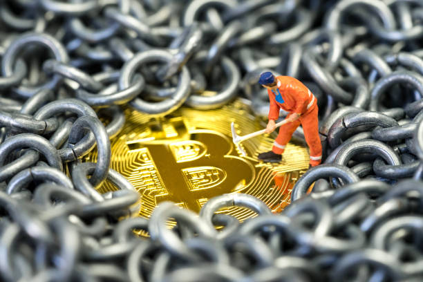 Bitcoin mining by miniature worker, small mini figure holding mattock digging on shiny golden physical Bitcoin Crpto currency coin surround by metal chains or blockchain concept Bitcoin mining by miniature worker, small mini figure holding mattock digging on shiny golden physical Bitcoin Crpto currency coin surround by metal chains or blockchain concept. mattock stock pictures, royalty-free photos & images