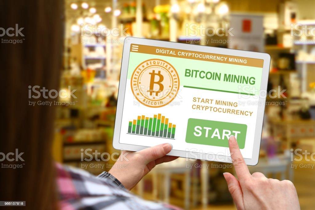 Bitcoin mining concept, meisje houdt de digitale tablet op de achtergrond wazig winkel - Royalty-free Bedrijfsleven Stockfoto