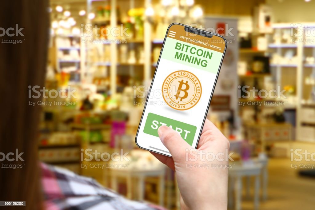 Bitcoin mining idea, girl with frameless phone on blurred shop background - Royalty-free Bitcoin Stock Photo