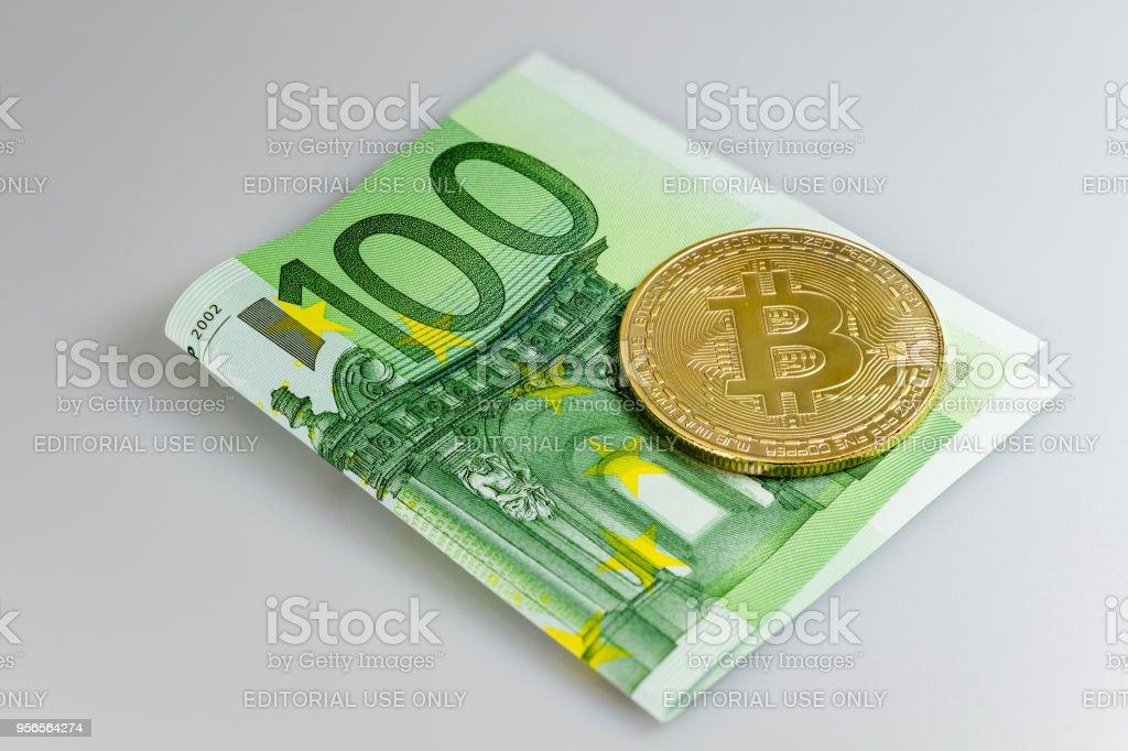 Ein Bitcoin auf ein 100 Euro-Schein vor einem weißen Hintergrund – Foto