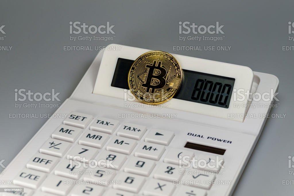 Ein Bitcoin auf einem weißen Rechner vor einem weißen Hintergrund – Foto
