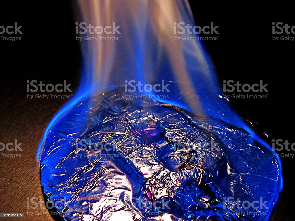 Bitcoin on fire. Real coin is burning with blue flame as symbol of hot price or critical fall stock photo