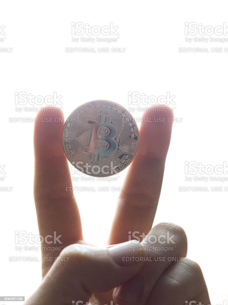 Bitcoin on the palm of a hand stock photo