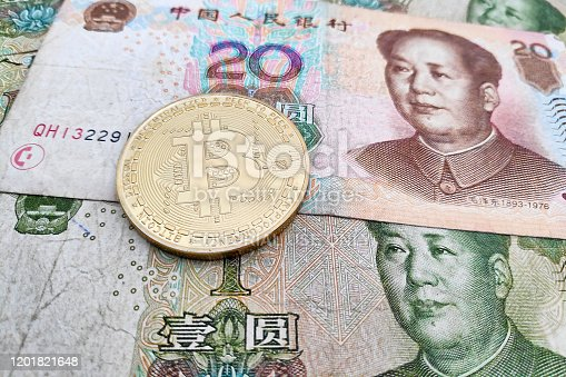 Close-up on a golden Bitcoin coin on top of a stack of Chinese Renminbi banknotes.