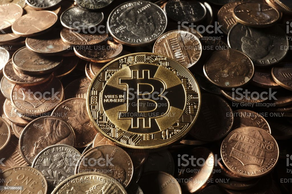 Bitcoin on top of dollar coins stock photo