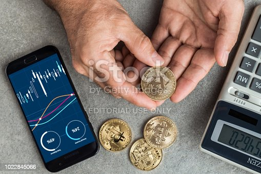 New York, USA - August 20, 2018: Businessman holding bitcoin memorial coins. Bitcoin is a cryptocurrency and a worldwide payment system invented by Satoshi Nakamoto in 2008.