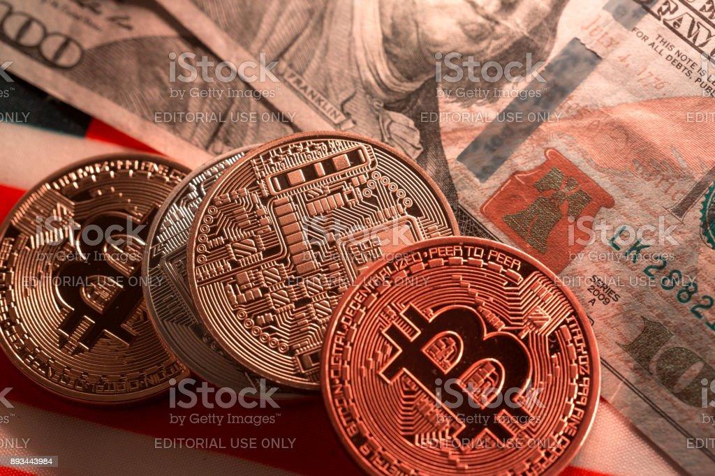 bitcoin sample illuminated in low light with 100 dollar bill stock photo