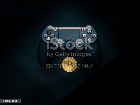 SHEFFIELD, UK - JUNE 2ND 2019: Shot taken from above of a Black Sony Playstation 4 controller sat above a Physical gold bitcoin on a dark black background