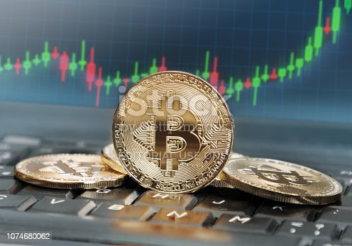 Bitcoins on keyboard with screen in the background displaying rising trend of its value