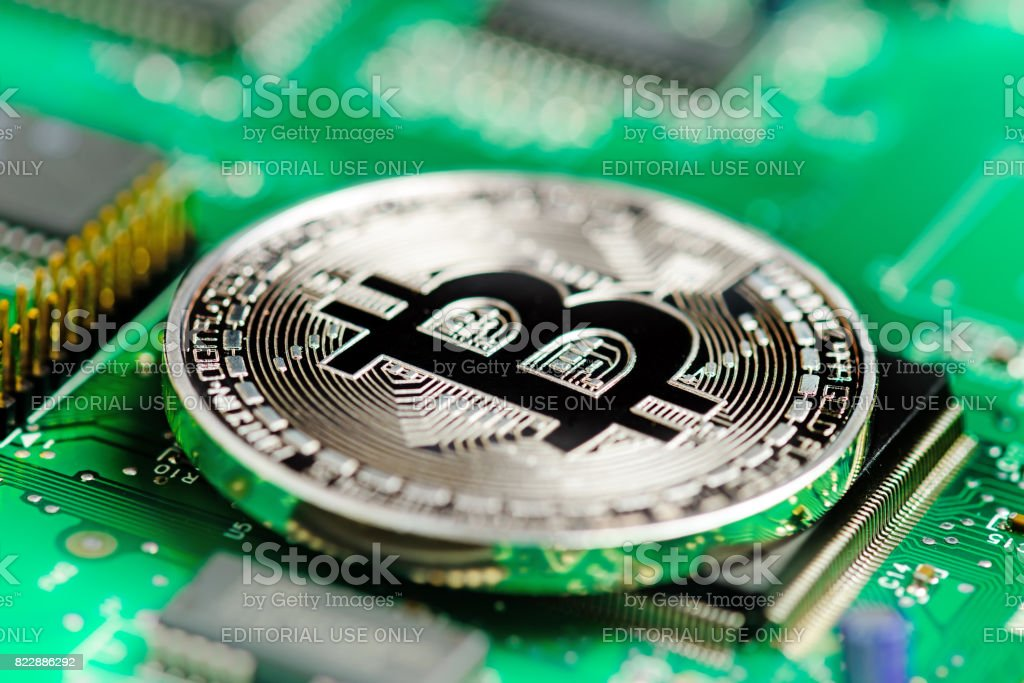 Moneda virtual Bitcoin en una placa de circuito - foto de stock
