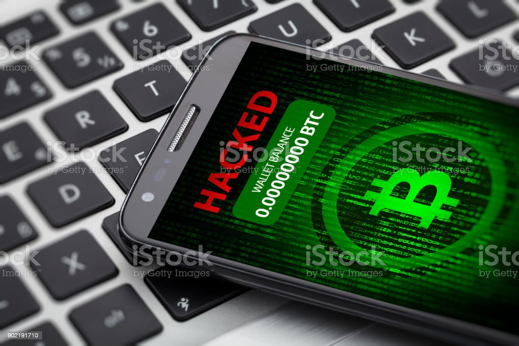 bitcoin wallet hacked message on smart phone screen. cryptocurrency theft comcept on smart phone screen. Big red hacked message and empty wallet. Phone on a laptop computer. Bitcoin Stock Photo