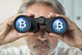 Businessman with binoculars looking to the future. Bitcoin, cryptocurrency concept.