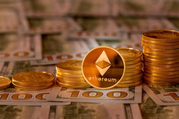 Bitcoins stacked on new design 100 dollar bills stock photo