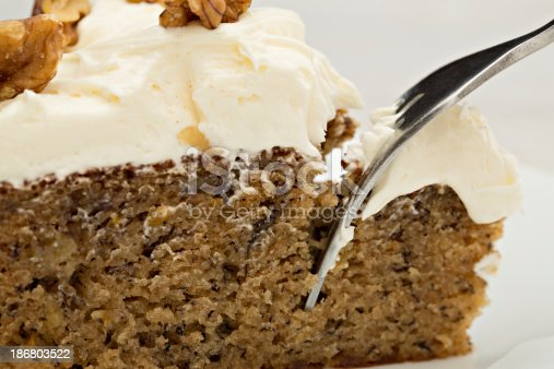 An extreme close up shot of a fork reaching for a bite of banana cake.