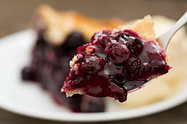 bite of blueberry pie - blueberry pie stock pictures, royalty-free photos & images