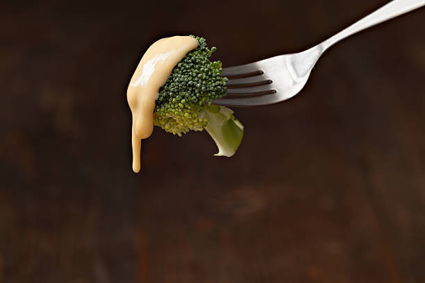 Bite Of Broccoli Wit Cheese Sauce A close up horizontal photograph of a fork with a bite of broccoli topped with golden cheese sauce. Isolated on black with ample copy space. melting stock pictures, royalty-free photos & images
