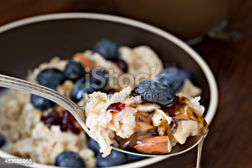A high angle extreme close up of a spoonful of oatmeal, nuts, blueberry and maple syrple.