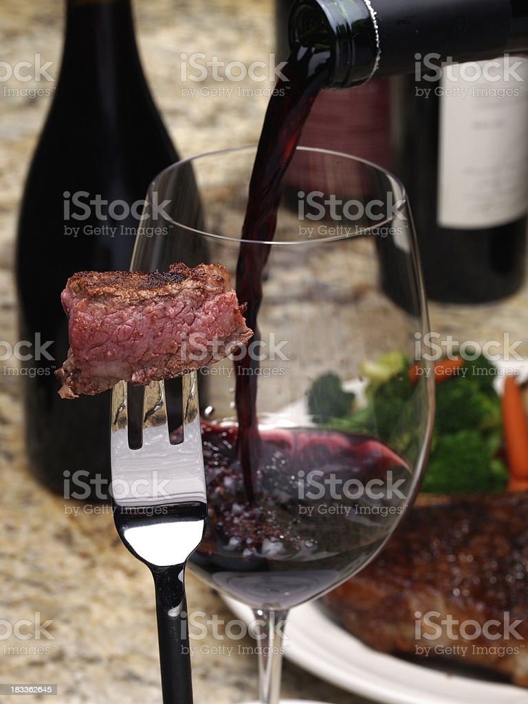 Bite of rare USDA prime steak on fork with wine glass filling behind....