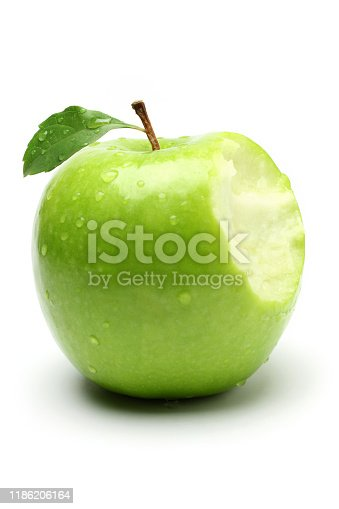 A bite on a green apple, isolated on white background.