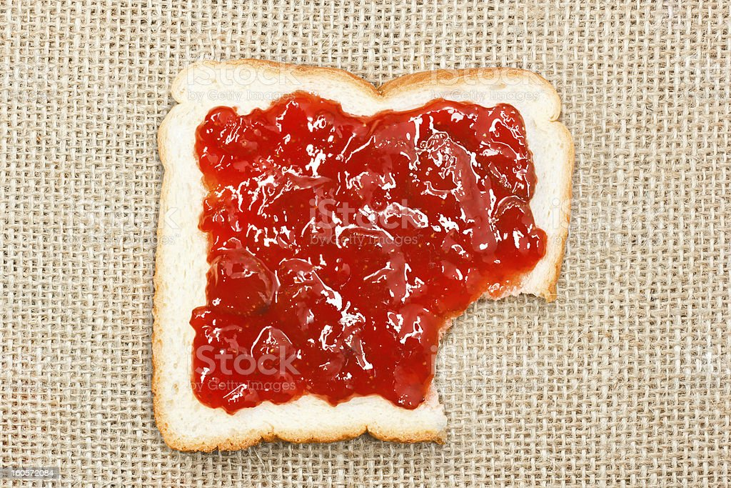 bited slice of bread with strawberry jam on sacking royalty-free stock photo