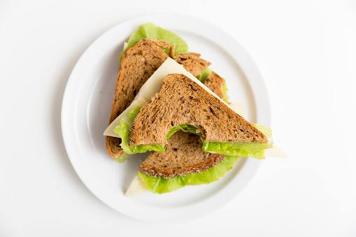 Bitten cheese and lettuce sandwich on a white plate. Lunch, break, healthy snack