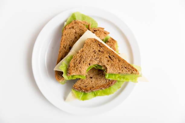 bitten ost och sallad smörgås på en vit platta. lunch, rast, hälsosamt mellanmål - tallrik uppätet bildbanksfoton och bilder
