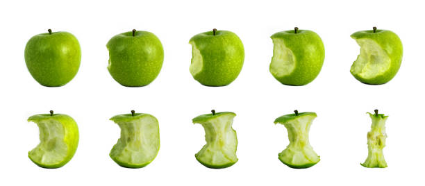 bitten green apples - stages of eating green apple - imploser photos et images de collection