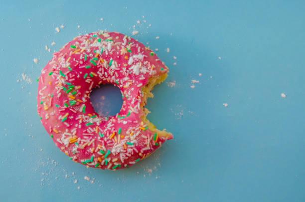 Mordu de donut rose sur fond bleu fariné vue de dessus - Photo