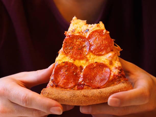 gebeten plak van pizza in de handen van de close-up van de persoon. de man in een paarse t-shirt met goed verzorgde handen eet peperoni pizza - dikke pizza close up stockfoto's en -beelden