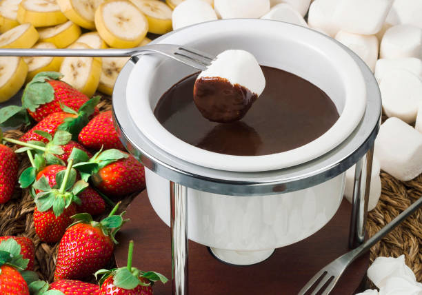 Bitter chocolate fondue with fresh fruits Bitter chocolate fondue with fresh fruits chocolate fondue stock pictures, royalty-free photos & images