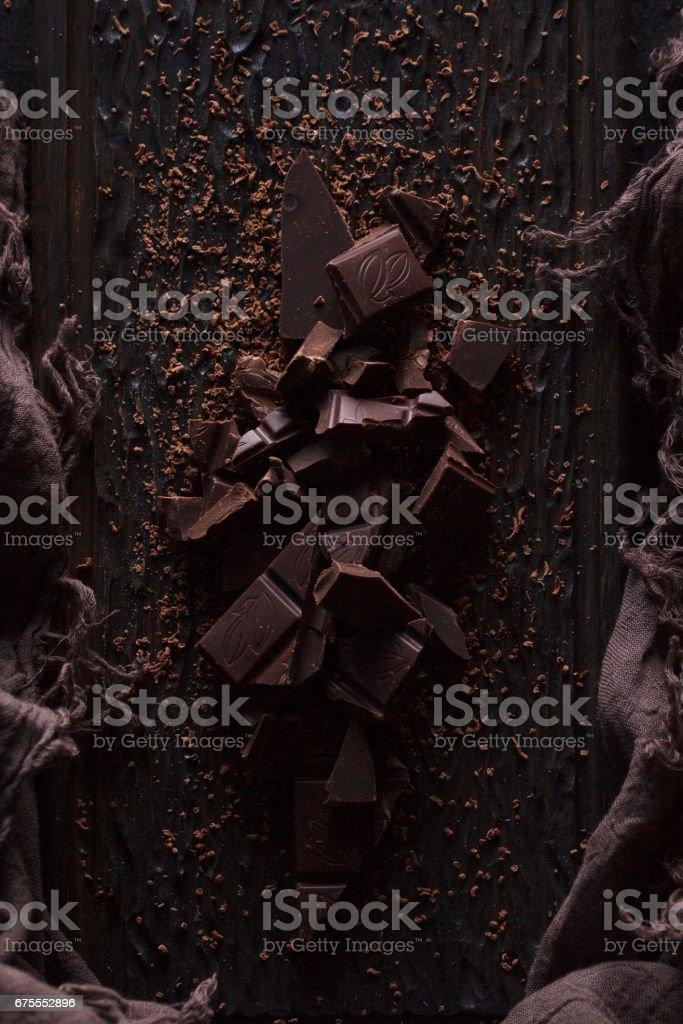 Bitter dark chocolate on a dark wooden background. Monochrome.