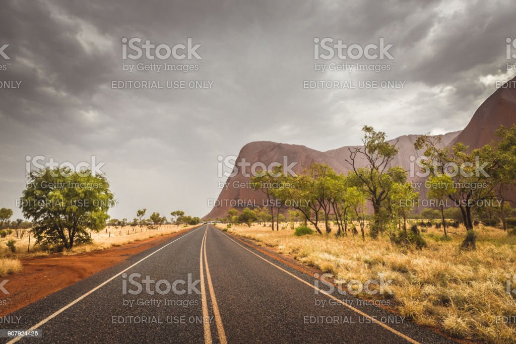 Bitumen road in the National Park leading to Uluru (Ayers Rock), Top Australian Tourist Destination on rainy day. stock photo