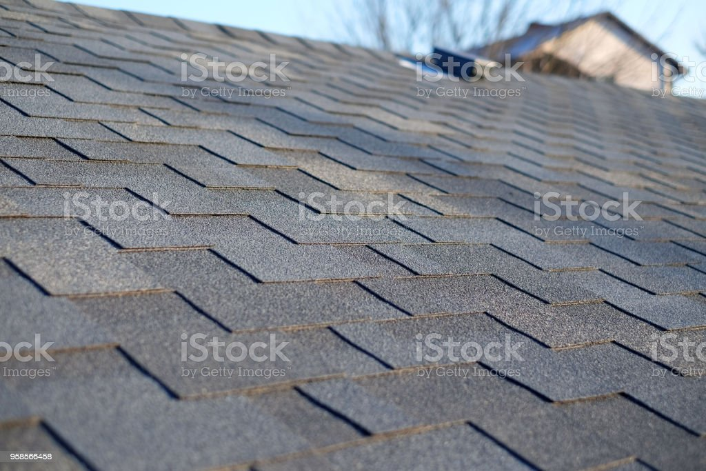 Bitumen tile roof. Roof Shingles - Roofing. Close up view on Asphalt Roofing Shingles . stock photo