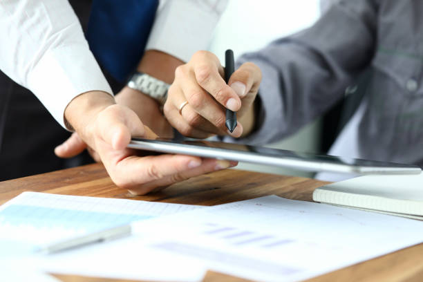 Biz communication between colleagues Focus on workers hands holding tablet. Manager giving for signature e-documents. Director signing important contract. Business concept. Blurred background between stock pictures, royalty-free photos & images