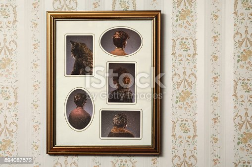 A picture frame hangs on a wall with an ornate frame and retro style, the people posing in the portrait facing the wrong direction, only the back of their heads and bodies visible.  Horizontal with copy space.