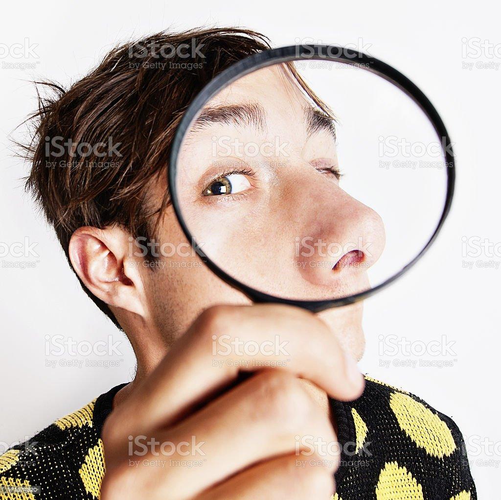 Bizarre boy examining face through magnifying glass stock photo