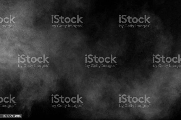 Photo of Bizarre forms of white powder explosion cloud against black background.