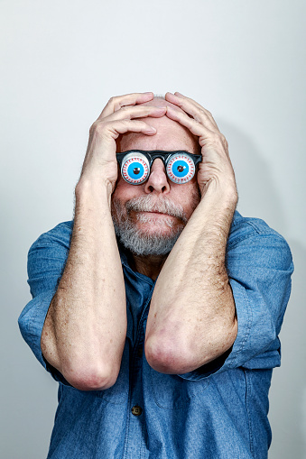 Bizarre senior adult man anxiously? fearfully? shyly? playfully? hugging his face and covering his head with his hands while wearing goofy spring loaded bloodshot eyeball novelty glasses.