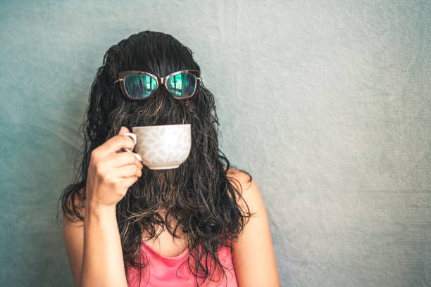 Bizarre woman Woman's face is covered with hair while she drinks coffee in the cup mask disguise stock pictures, royalty-free photos & images