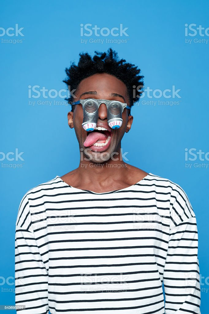 Bizzare afro american young man wearing funny eyes mask Portrait of crazy afro american guy wearing striped long sleeved t-shirt and funny eyes glasses, staring at the camera. Studio shot, blue background.  Adult Stock Photo