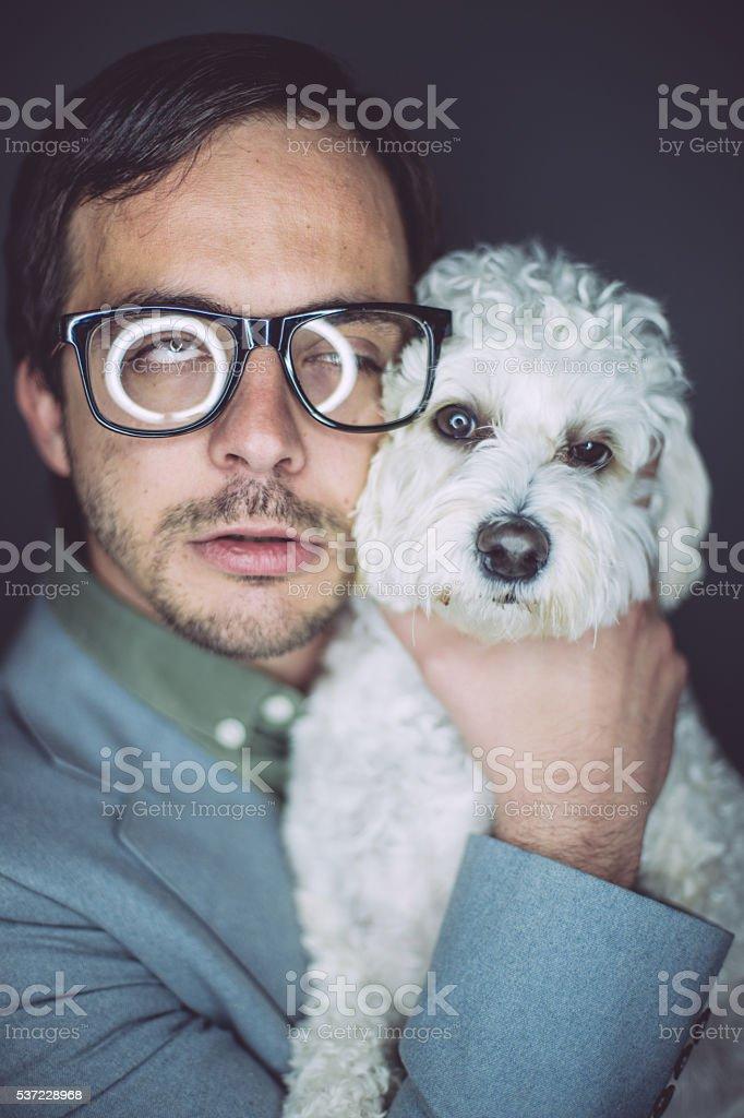 Bizzare dweeb holding lovely little dog stock photo