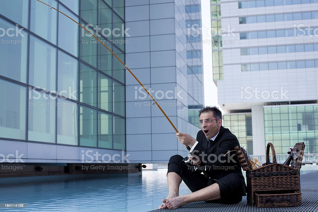 Bizzarre Businessman Fishing at Lunch Break royalty-free stock photo