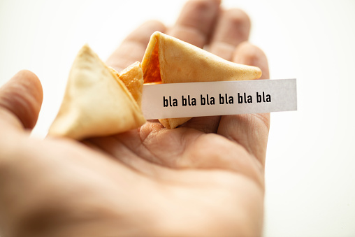 A hand taking out paper from a broken fortune cookie. Blah.