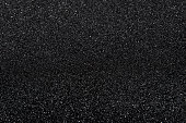 The texture of black stone (minerals) crumb. Black abstract background with defocused area. Top view.