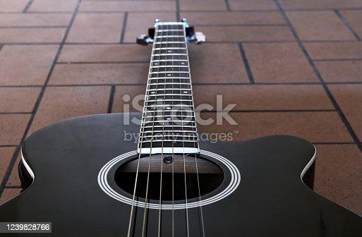 1014432572 istock photo Black acoustic guitar on the brick floor. Closeup top-down photo. 1239828766